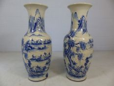 Pair of large oriental blue and white vases depicting mountain scenes. Approx height of each 83cm