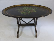Ebonised Tilt top oval table decorated with flora and forna