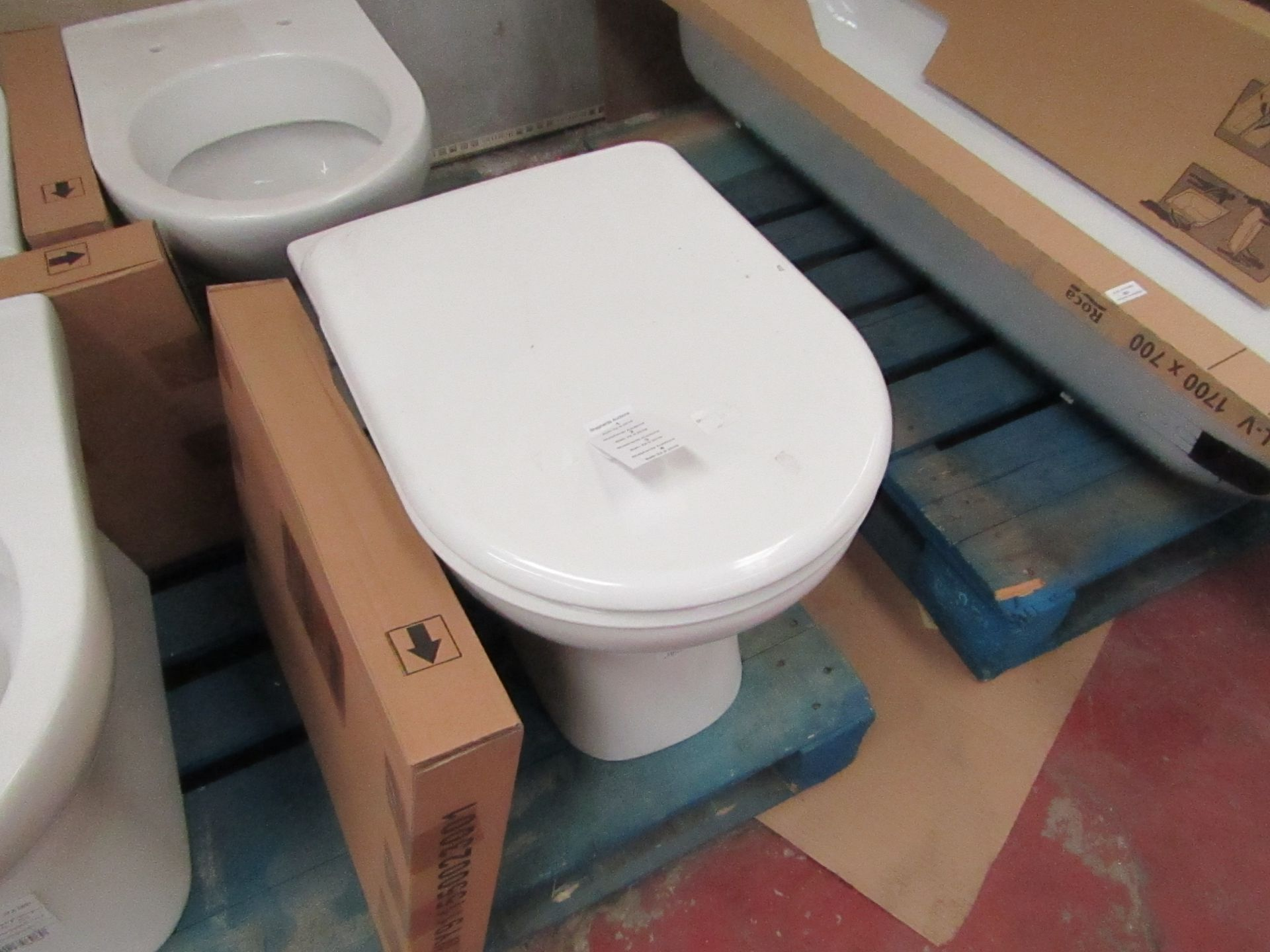Lotto 1 - Jika Deep floor mounted back to wall toilet pan with toilet seat, new
