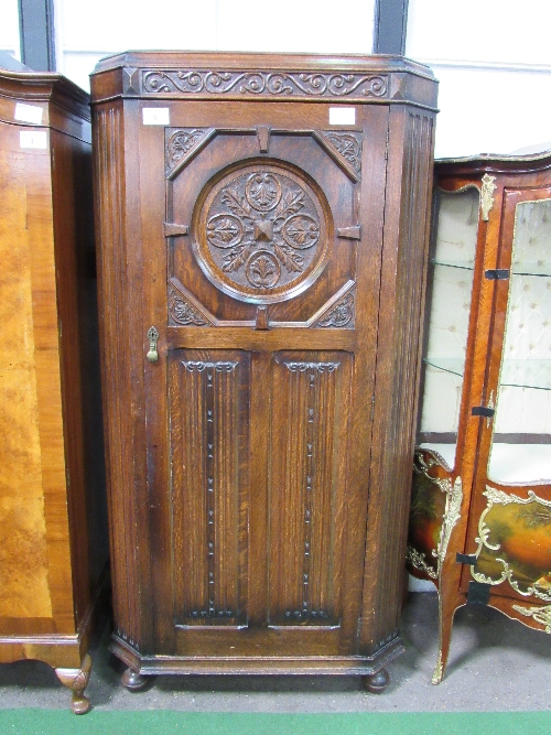 Lot 5 - 1920's oak hall cabinet with canted reeded sides, carved medallion above linen fold carving to door,