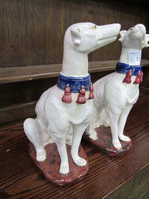 Lot 10 - Pair of Majolica greyhound figures painted white with blue collars, height 36cms. Estimate £50-80