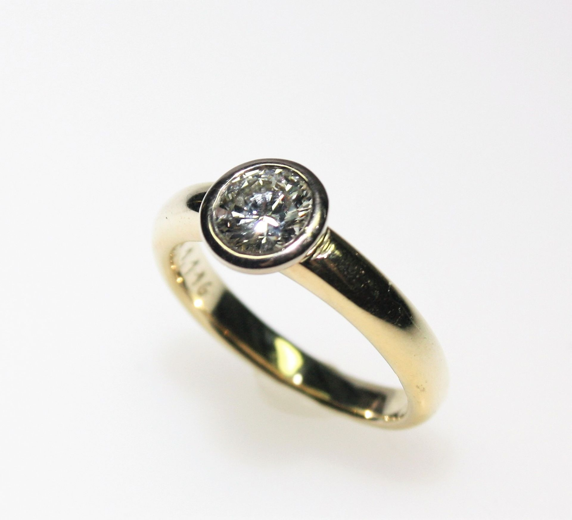 Los 55 - Moderner, goldener Ring 750/f gest., in Zarge gefasst ein Diamantsolitär in Brillantschliff ca. 1,11