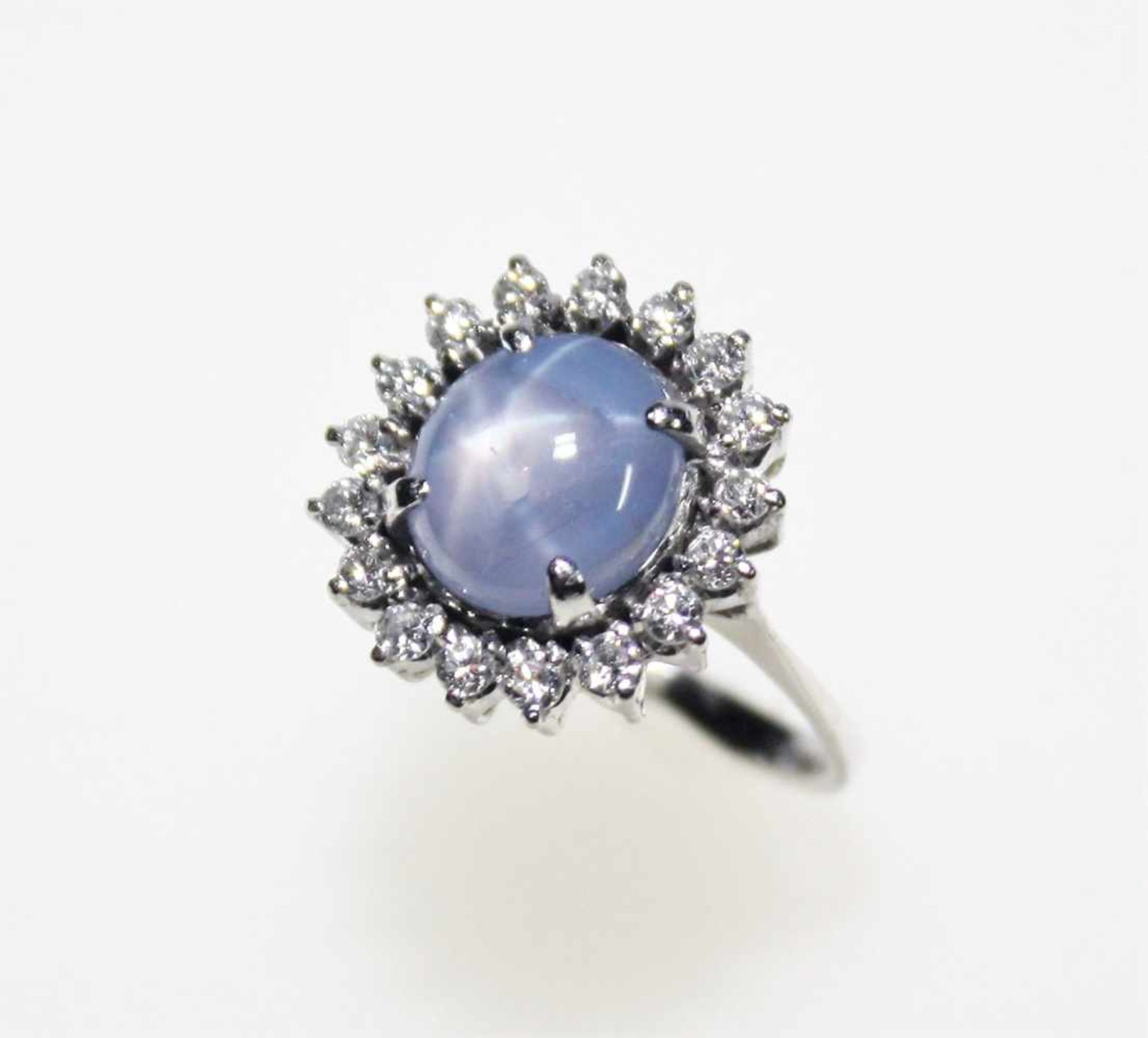 Weißgoldring 585/f gest. mit einem blass-blauen Sternsaphir umgeben von Kleindiamanten in
