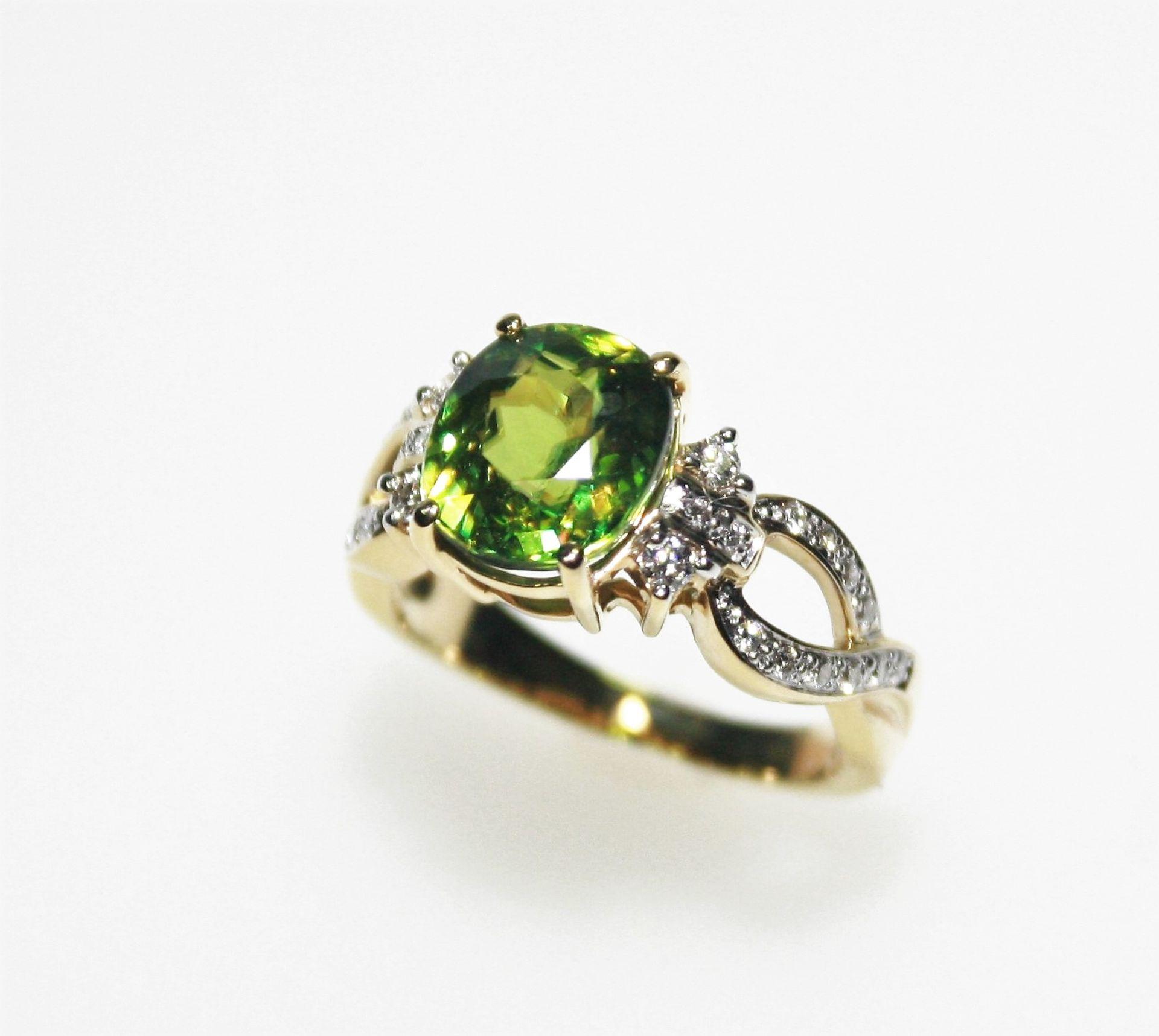 Moderner, goldener Ring 750/f gest. mit grünem Schmuckstein, vermutlich Peridot, seitlich