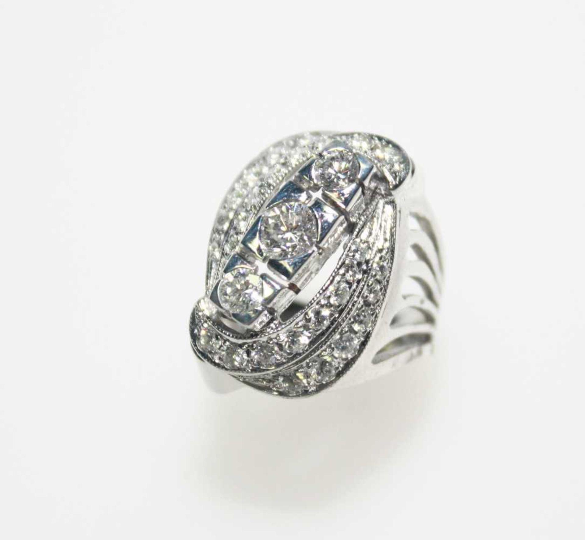 Größerer Weißgoldring der 60er Jahre 585/f gest., zur Mitte drei Diamanten in Brillantschliff zus.