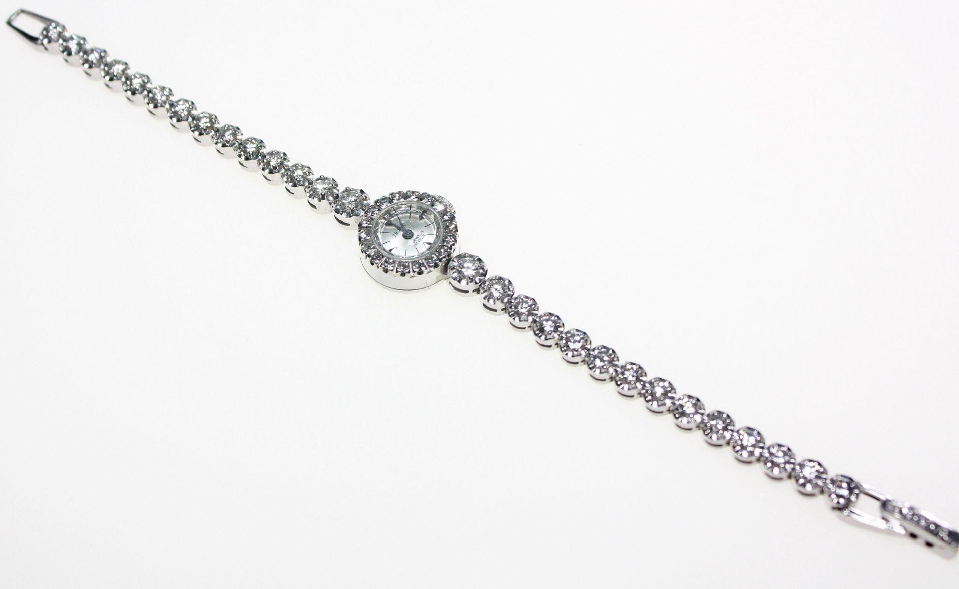 Schmale, weißgoldene Damen-Armbanduhr mit fest angearbeitetem Ansatzband 585/f gest., rundes