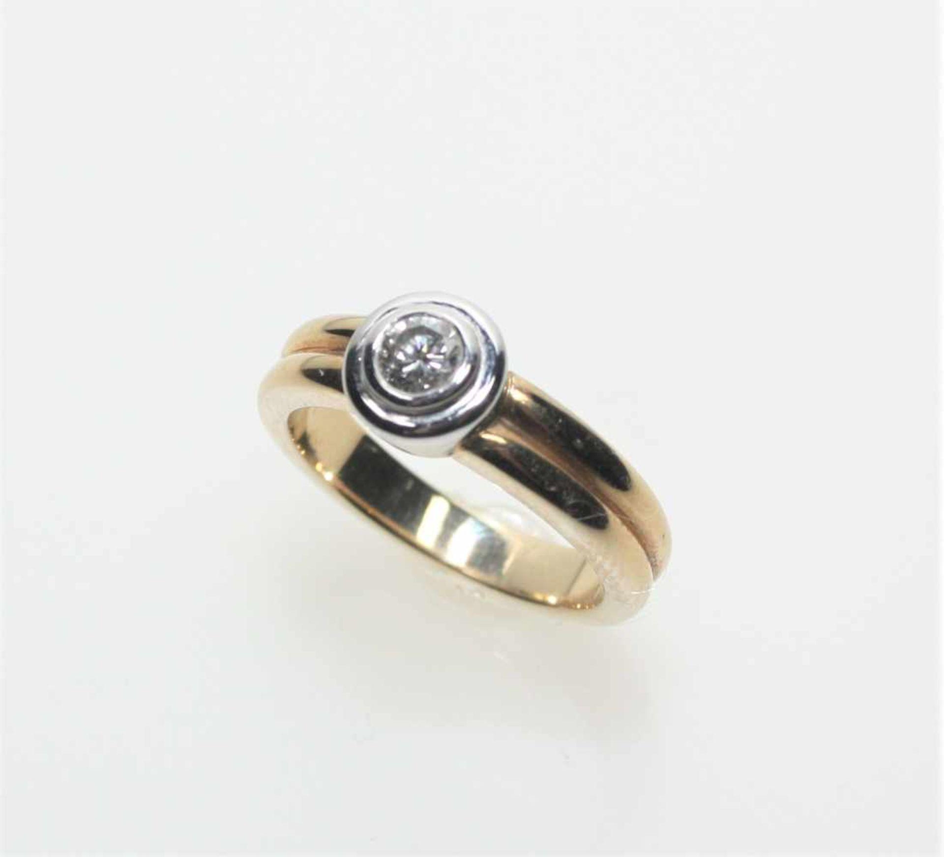 Los 13 - Moderner, goldener Ring 585/f gest., in weißgoldener Zarge ein Diamant in Brillantschliff ca. 0,30