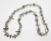 Kleine Kette aus unregelmäßigen, grauen Perlmuttteilen, unterbrochen von kleinen Goldstegen,