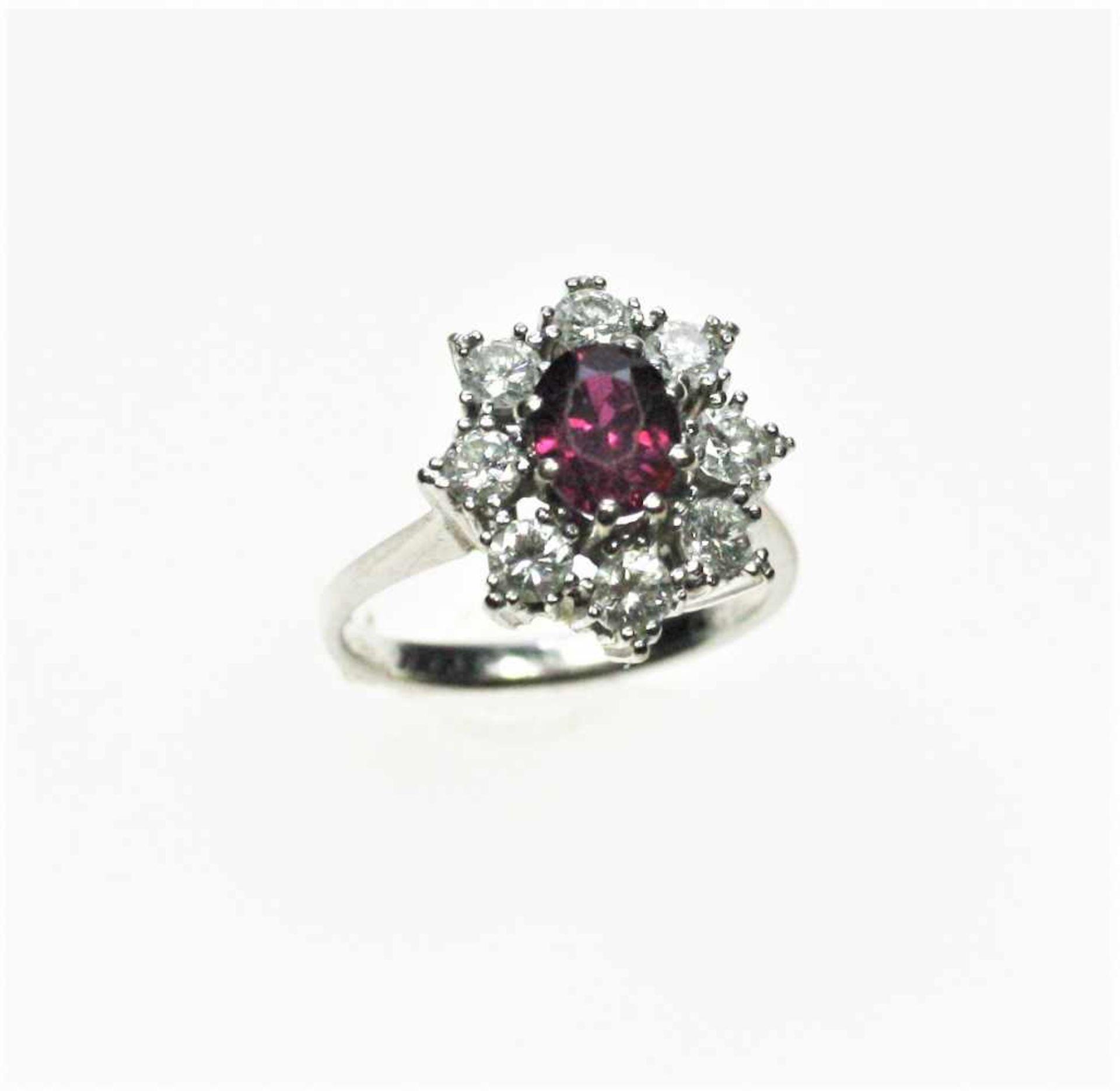 Weißgoldring 750/f gest. mit einem ovalen Rubin ca. 0,80 ct (abgetragen) umgeben von Diamanten in