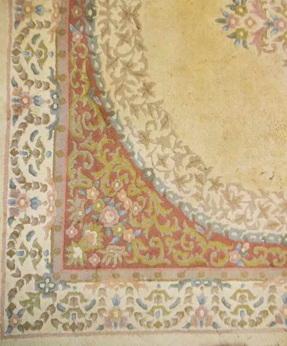 Lot 318b - A large Persian style cream ground carpet with floral decoration