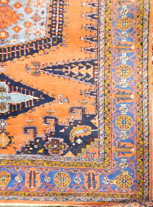 Lot 323 - A large Persian pink, blue and green ground fringed and bordered rug, central medallion within multi