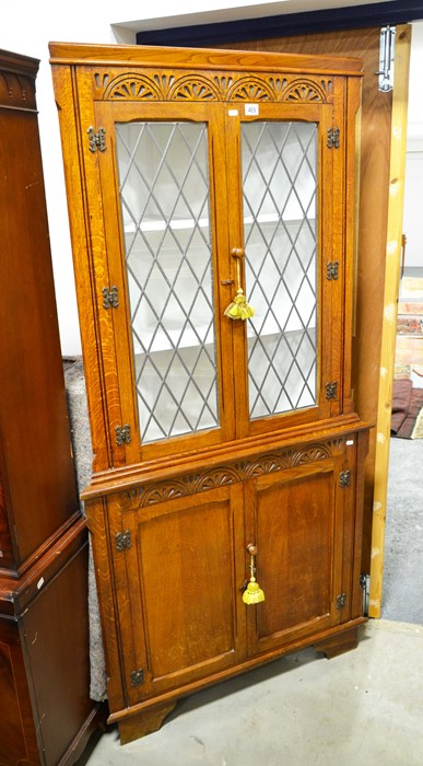 Lot 469 - An oak corner cabinet fitted leaded windows. Height 185cm