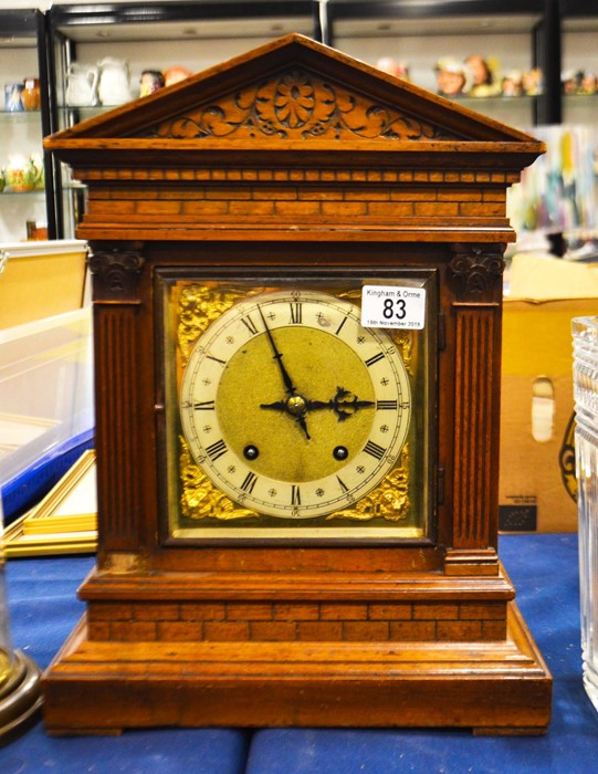 Lot 83 - A W. & H. Son oak architectural cased mantle clock, sloped arched top with carved floral decoration.