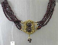 Kropfkette, 19. Jh.Silberschloss, vergoldet, Reliefarbeit, 2 Granatblumen, 6-reihig, Granatketten, ö