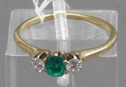 Damenring14 kt. Gelbgold, 1 Smaragd, 2 kleine Altschliffdiamanten, zusammen ca 0,10 ct.,