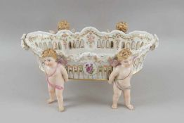 Liebliche Jardiniere / Tafelaufsatz, bemaltes Porzellan, getragen von vier Amoretten /Putten, auf