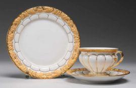 """Kaffeegedeck """"X-Form""""Weiß, glasiert. Reliefdekor. Reiche Staffage in Matt- u. Glanzgold."""