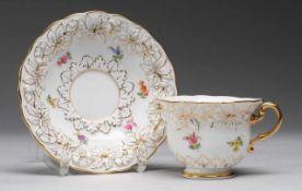 Tasse mit UTWeiß, glasiert. Floraler Reliefdekor. Polychrome Bemalung mit Streublüten. Goldränder u.