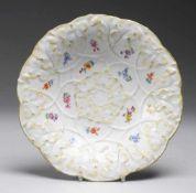 Schale mit ReliefdekorWeiß, glasiert. Runde gemuldete Form. Weinlaub-Reliefzierrat. Polychrome