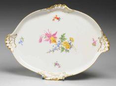 Ovalplatte mit BlumenmalereiWeiß, glasiert. Rocaillen-Reliefzierrat. Polychrome Bemalung mit