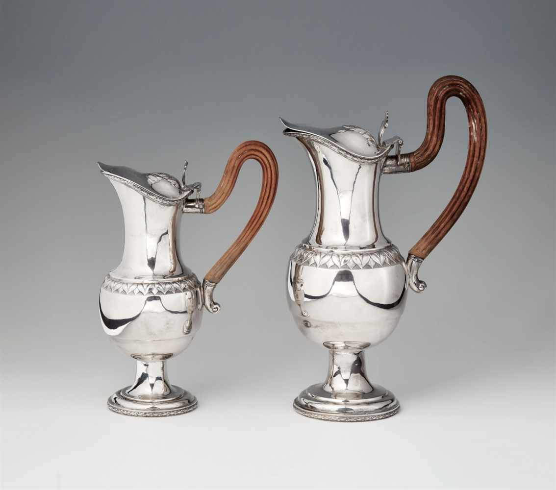 Lot 335 - A pair of Augsburg silver wine pitchersPear-shaped corpus on waisted foot with hinged lid and
