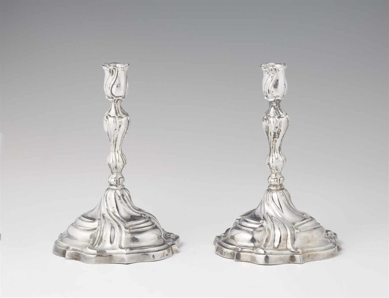 Lot 328 - A pair of Augsburg silver candlesticks by Johann HeckenauerRound scalloped base supporting a twist