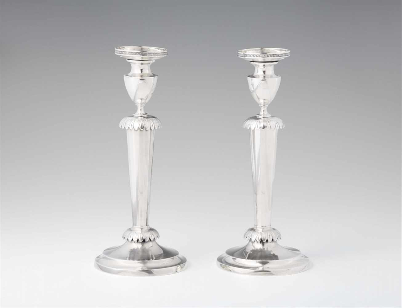 Lot 352 - A pair of Kassel silver candlesticksRound bases supporting fluted tapering shafts with palmette form