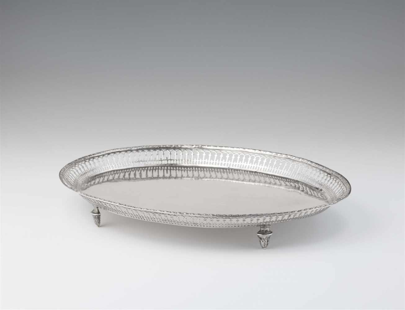 Lot 341 - A Neoclassical Augsburg silver platterOval tray on four supports with pierced gallery rim. L 35.5; W