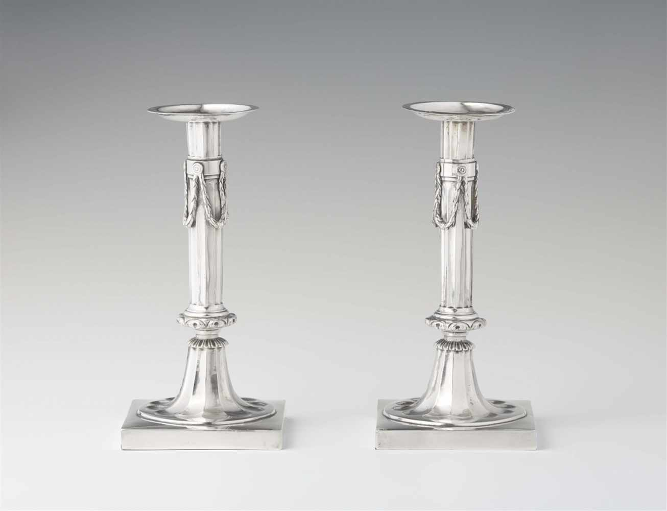 Lot 353 - A pair of Cologne silver candlesticksFluted columns with festoons on square bases. H 22.5 cm, weight