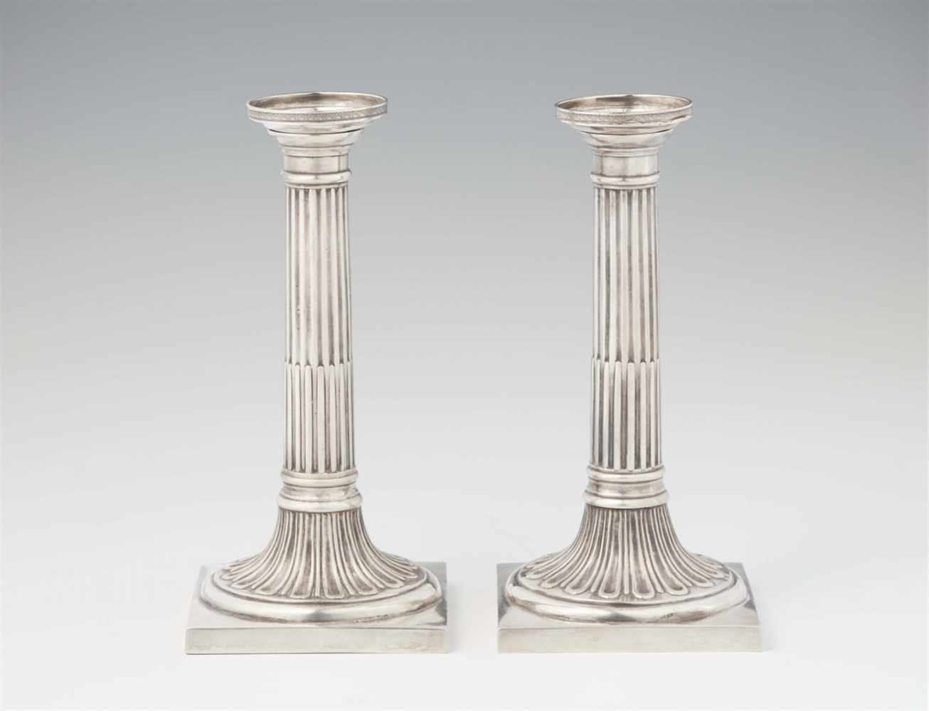 Lot 339 - A pair of Neoclassical Augsburg silver candlesticksFluted column shafts resting on square plinths. H