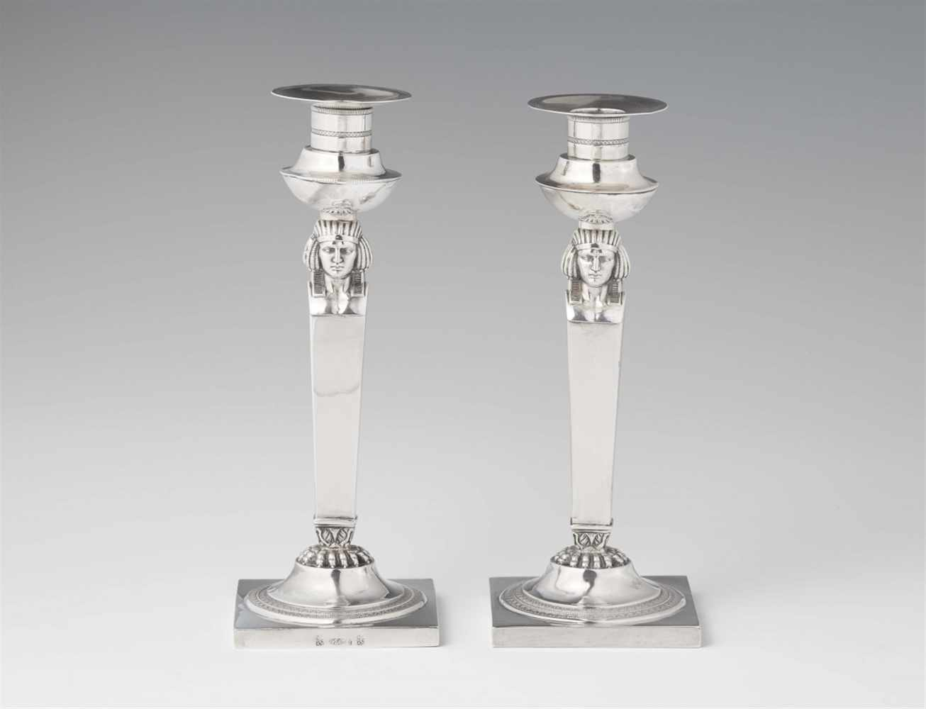Lot 348 - A pair of Frankfurt Empire silver candlesticksSquare plinths supporting tapering shafts with
