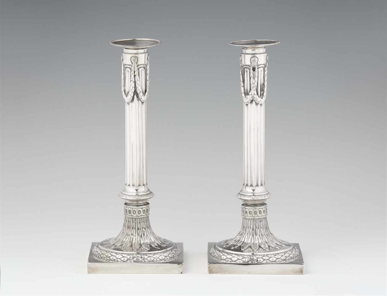 Lot 337 - A pair of Mannheim silver candlesticksFluted shafts supported by square plinths. H 26 cm, weight 720