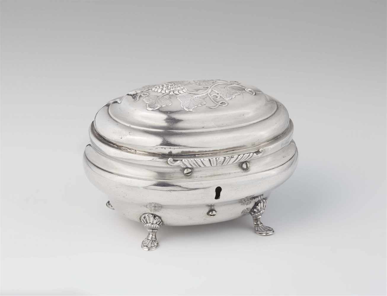 Lot 356 - A Naumburg silver sugar boxBombé form box on four shell supports, the hinged lid with grapevine