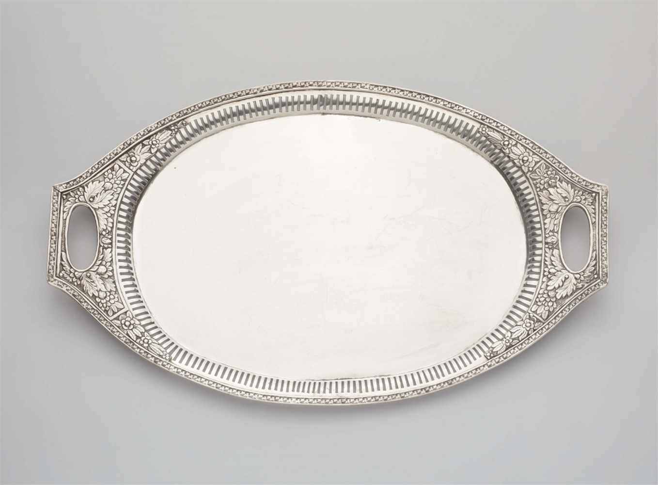 Lot 357 - A Neoclassical silver platterOval tray. Pierced rim with acanthus and flowerhead reliefs. L 54; W 33
