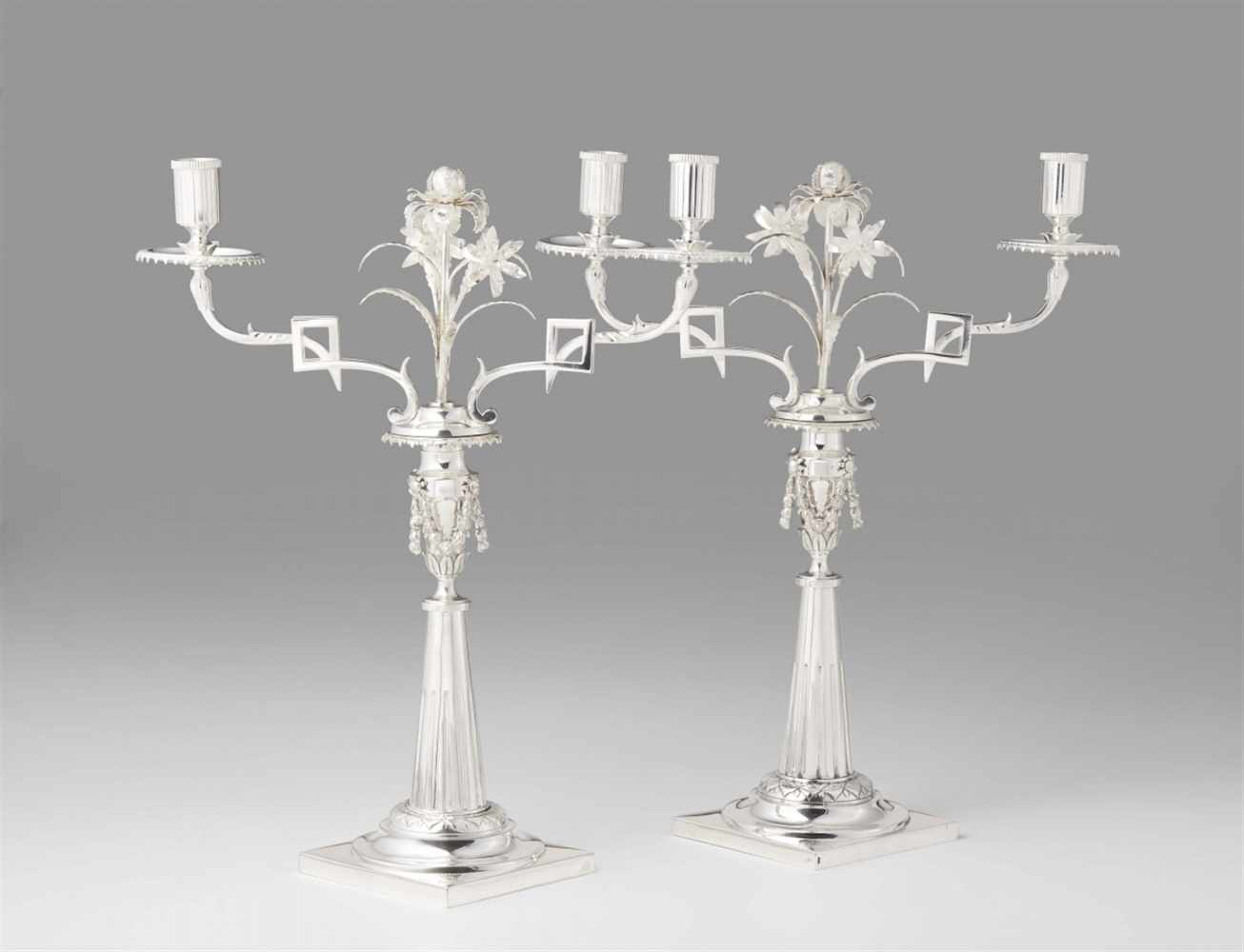Lot 338 - A pair of Augsburg silver candelabraTapering fluted shafts supported by square plinths with small