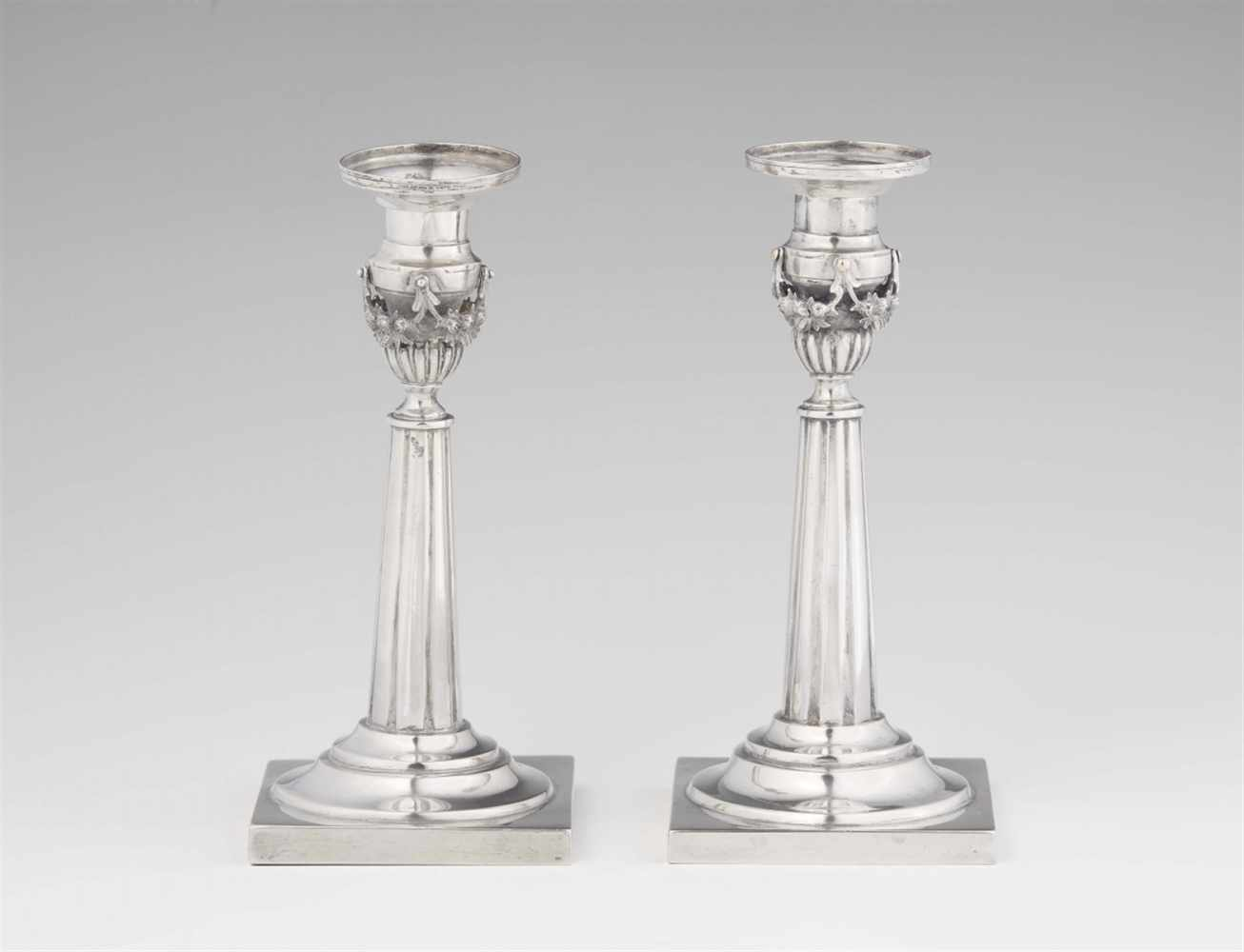 Lot 355 - A pair of Weißenfels silver candlesticksTapering fluted shafts resting on square plinths. H 18 cm,
