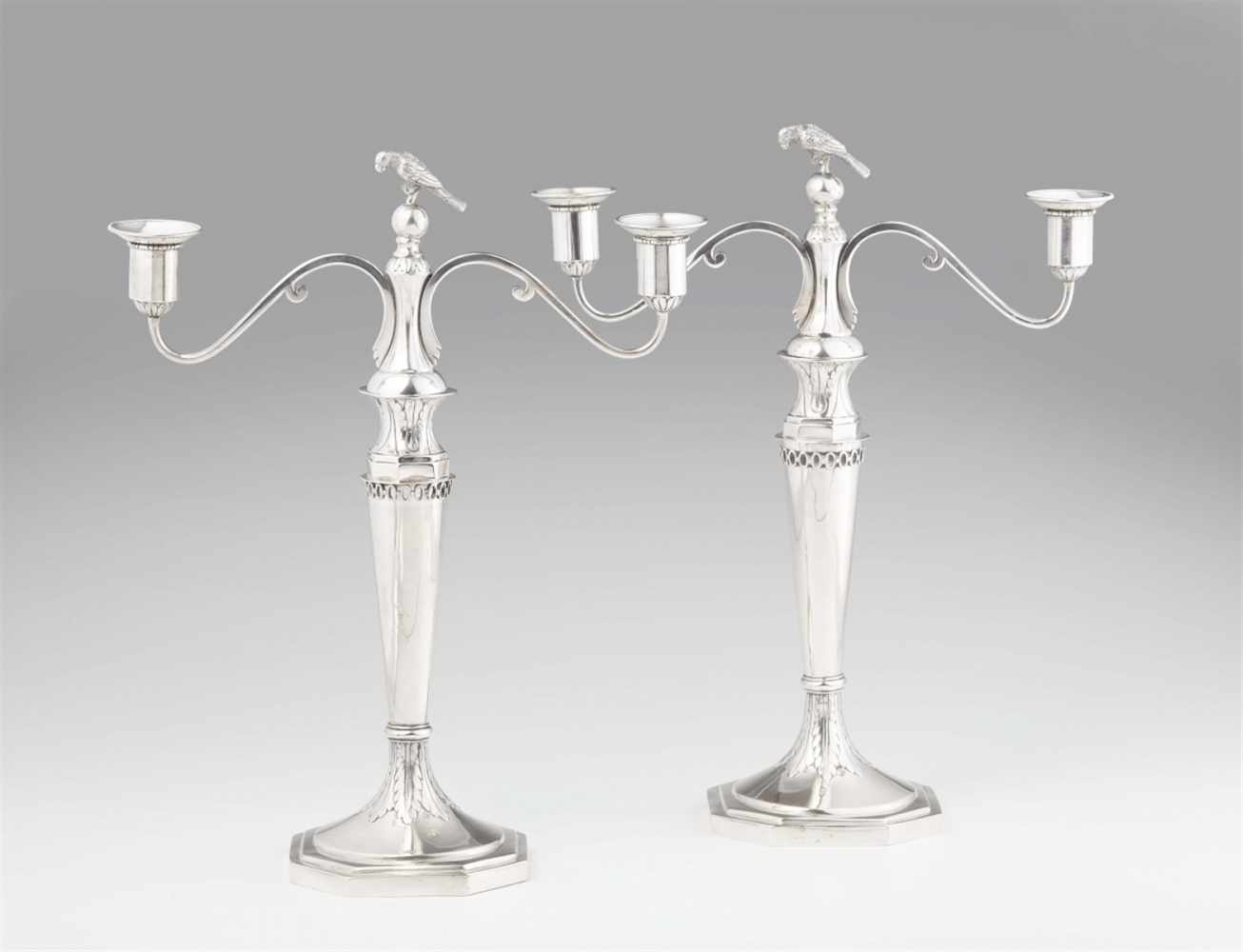 Lot 351 - A pair of Dresden silver candelabraSmooth conical shafts resting on octagonal bases, with loosely