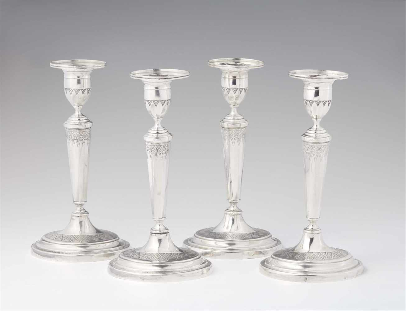 Lot 343 - A set of four Augsburg silver candlesticksOval bases supporting fluted shafts and vase shaped