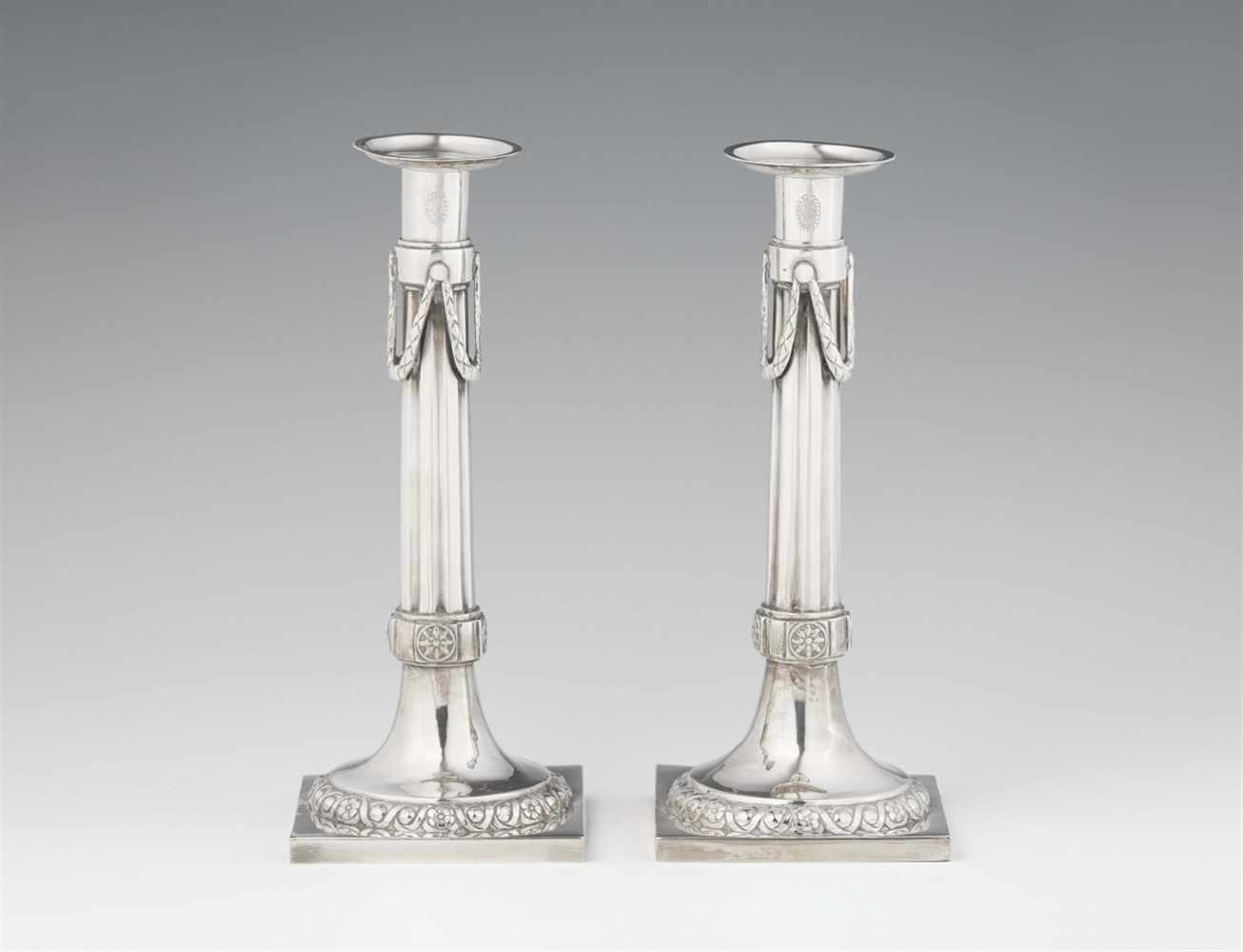 Lot 336 - A pair of Augsburg silver candlesticksFluted shafts on square plinths. H 25 cm, weight 674 g.