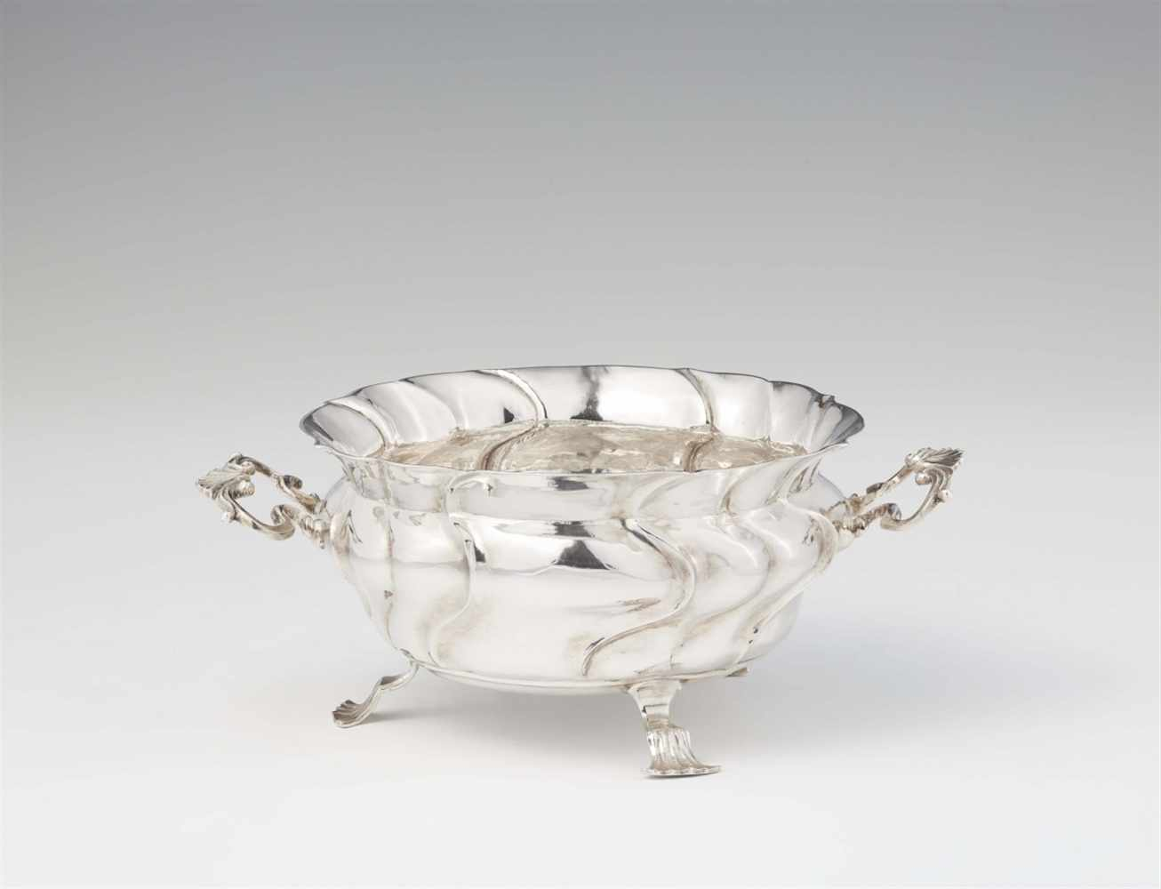 Lot 330 - An Augsburg Rococo silver dishBombé form twist fluted dish with scroll handles resting on three