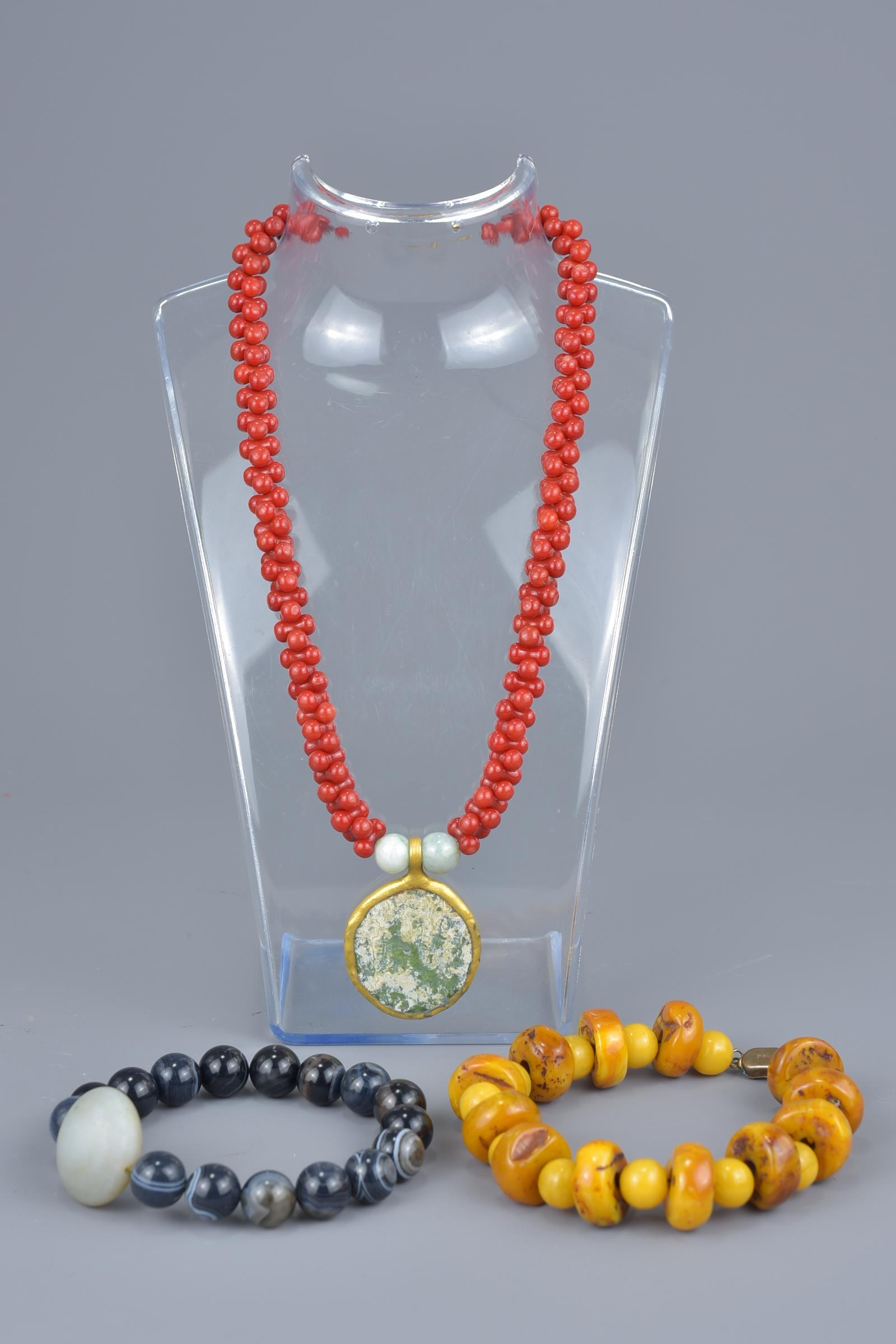 Lot 39 - One beaded necklace with glass pendant and two beaded bracelets.