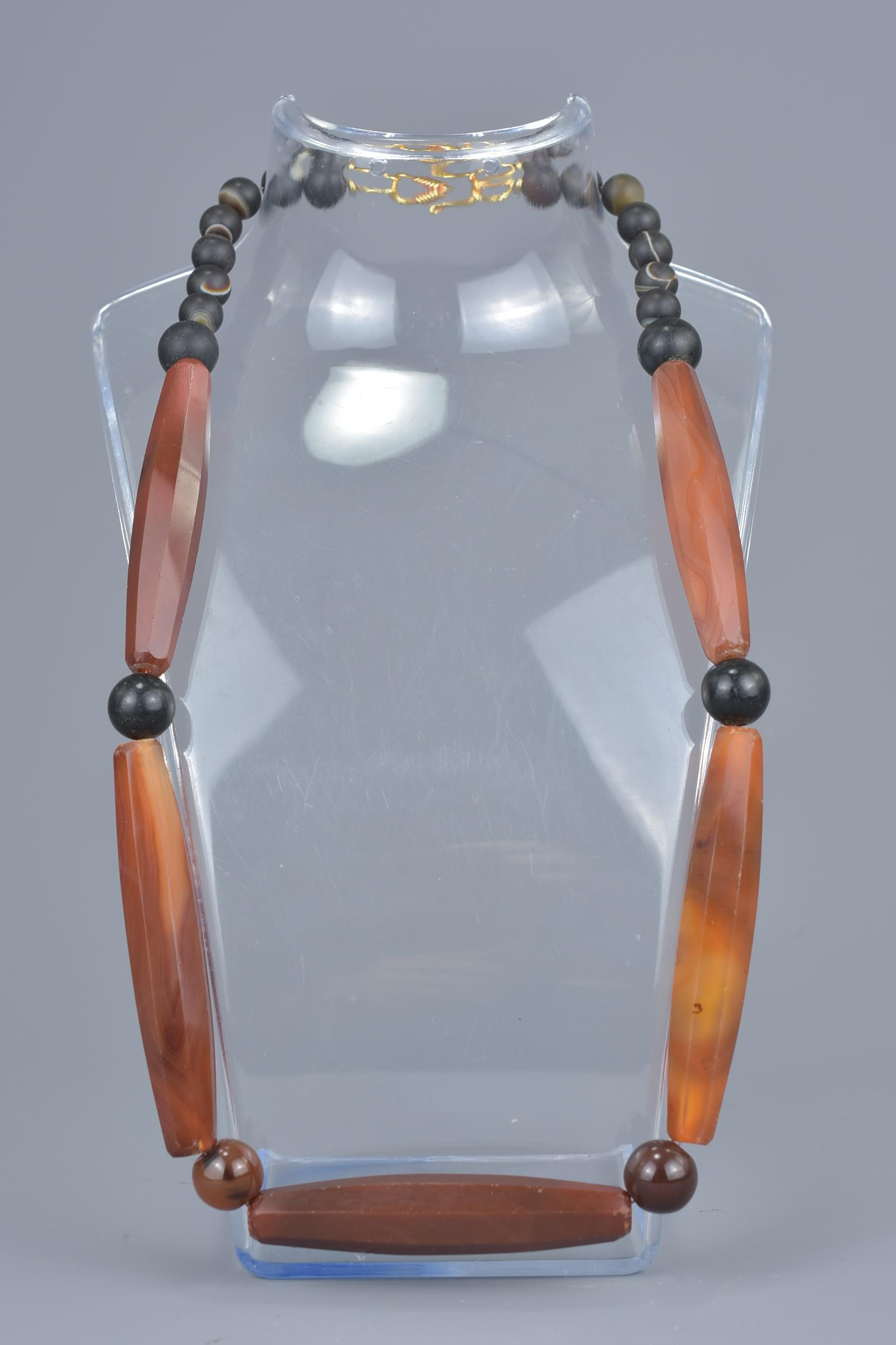 Lot 38 - A string of five long agate beads together with twenty small agate beads in a necklace.