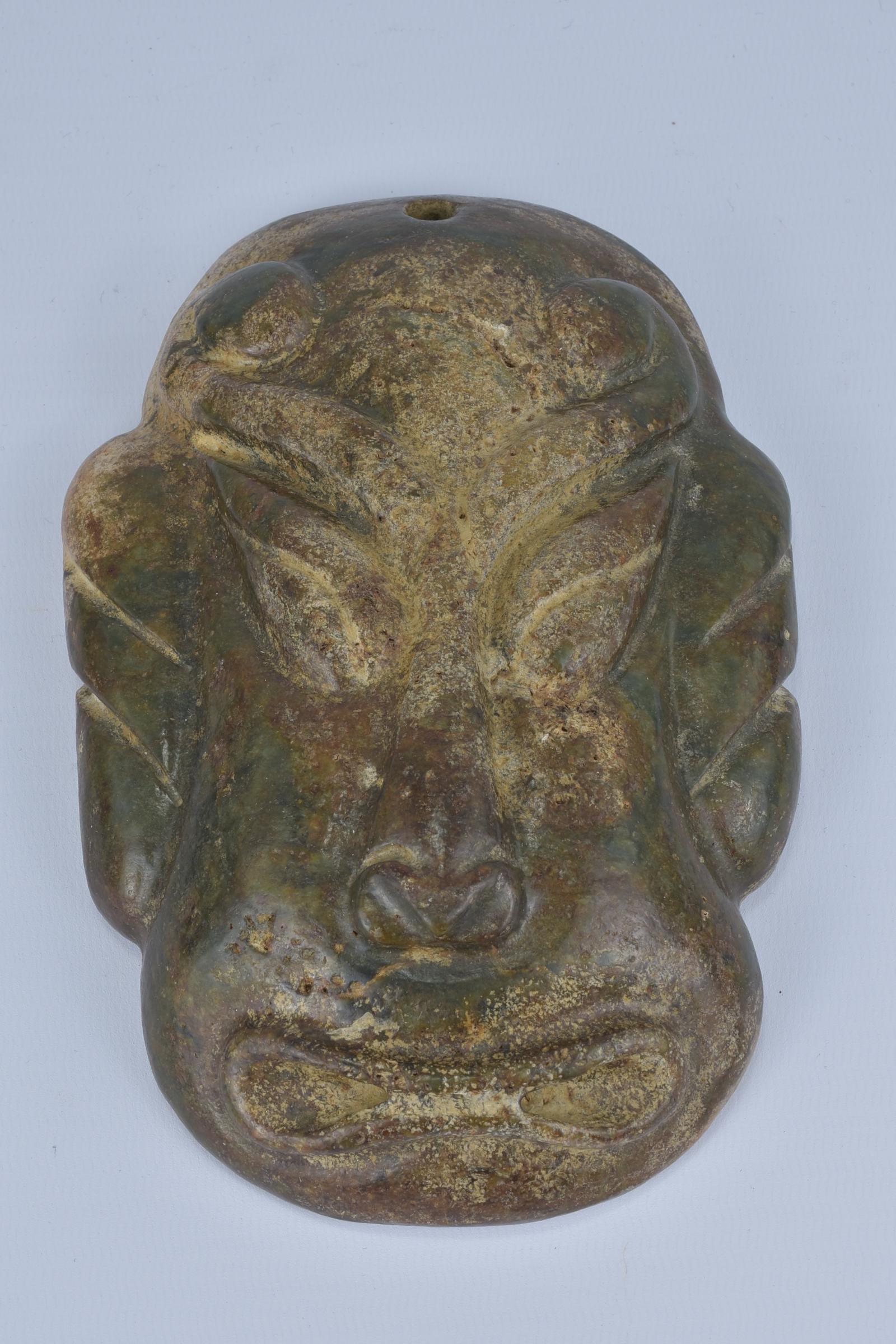 Lot 8 - A large archaic style stone mask pendant. 9cm width