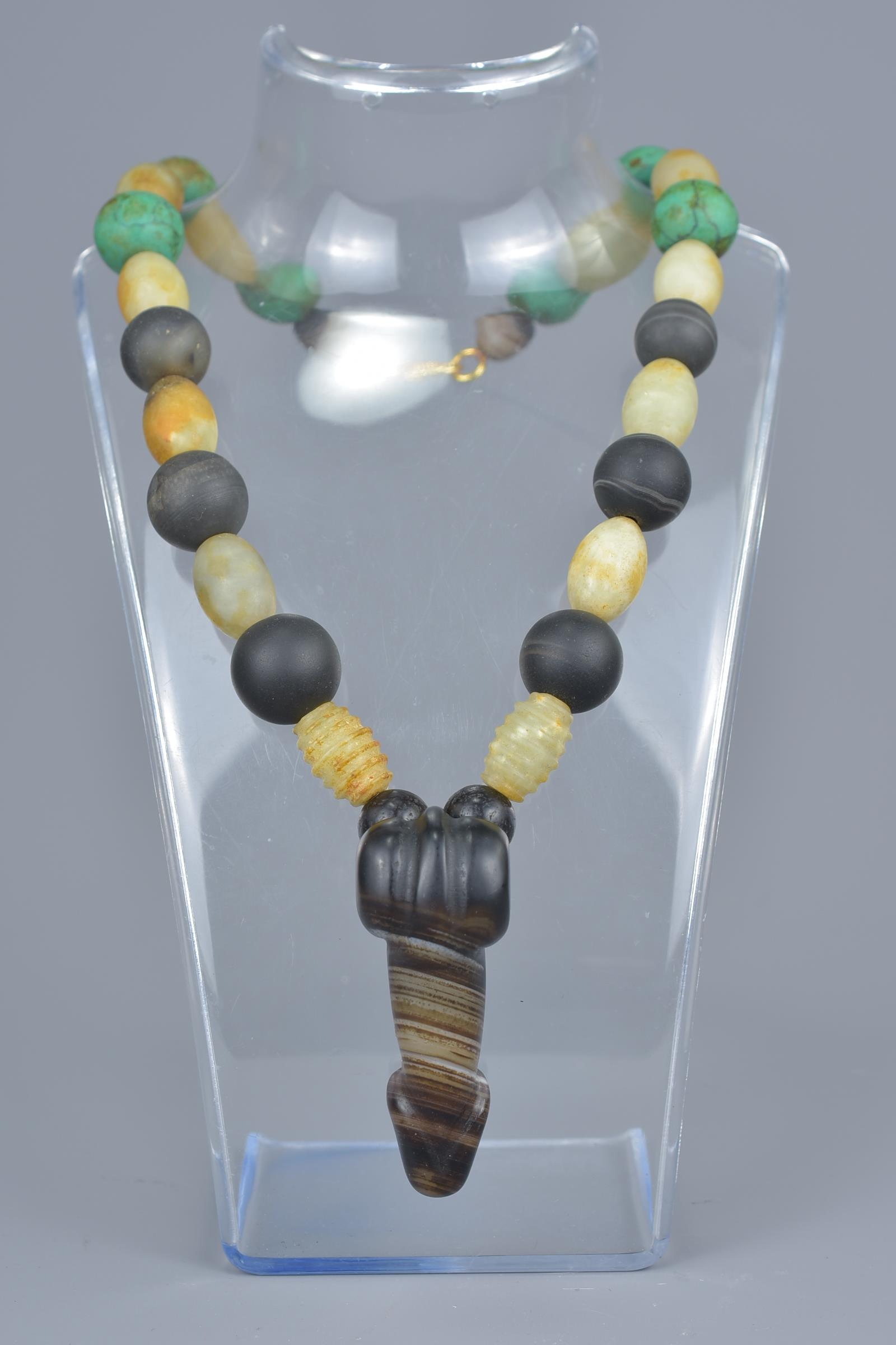Lot 36 - An agate phallic pendant on beaded necklace.