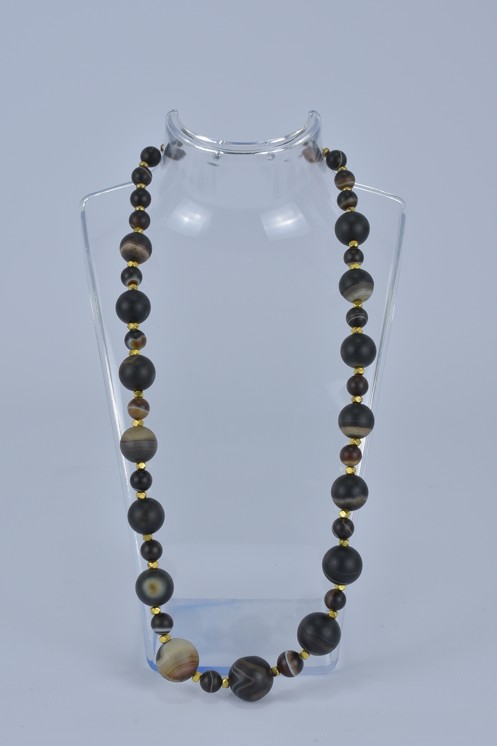 Lot 51 - A banded Agate necklace with Gold Metal Spacers.