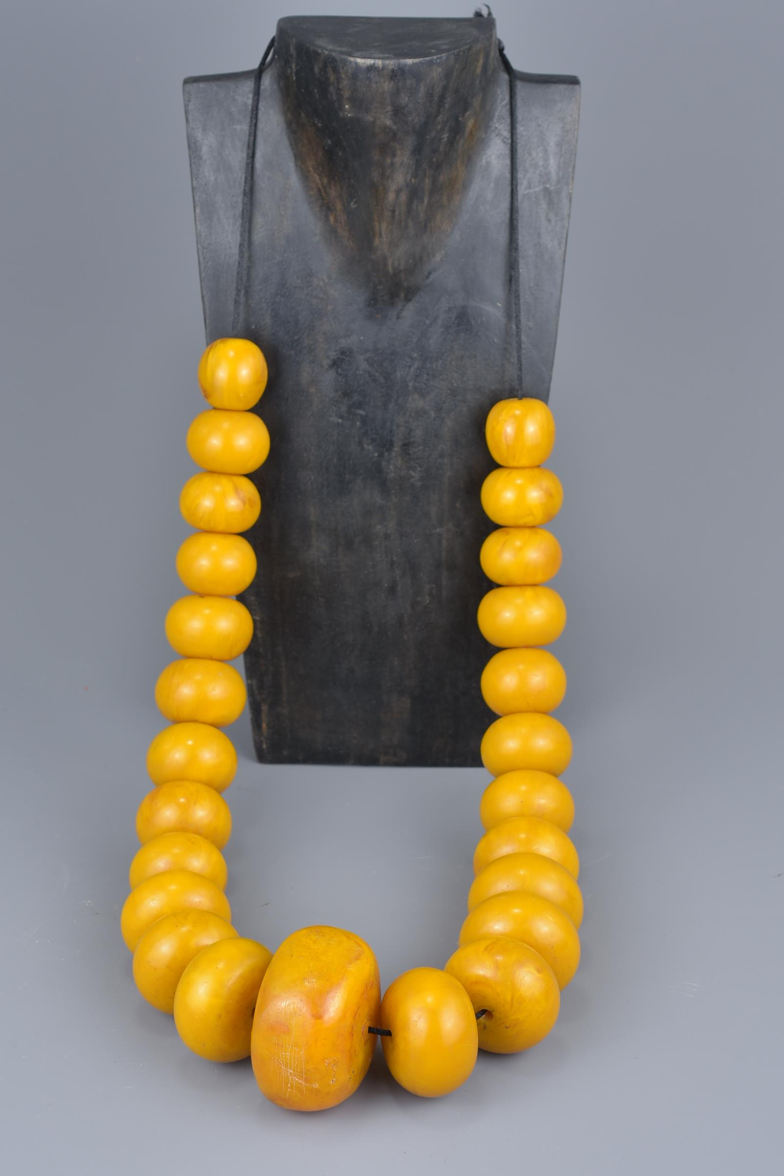 Lot 31 - A large Moroccan amber resin bead necklace on string.