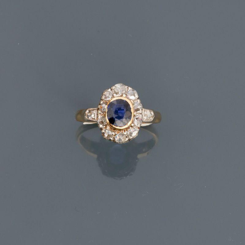 Lot 21 - Bague deux ors, 750 MM, centrée d'une pierre bleue entourée de diamants taille [...]