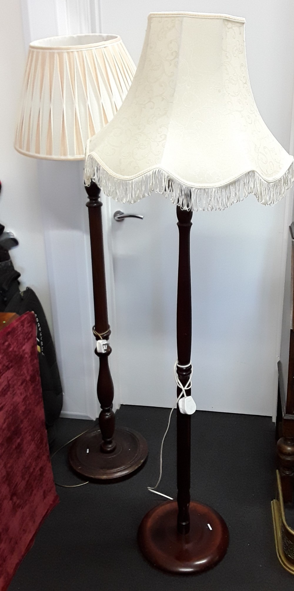 Lot 486 - Two turned mahogany standard lamp stands with shades