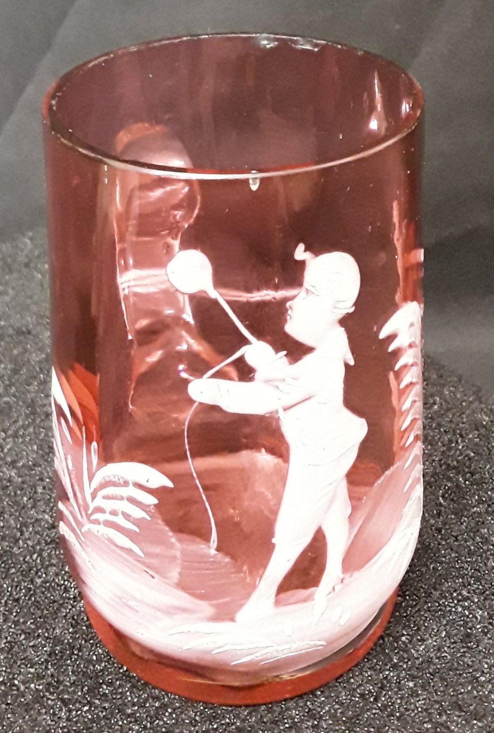 Lot 20 - A hand blown and rolled Cranberry glass beaker with hand painted white enamelling.