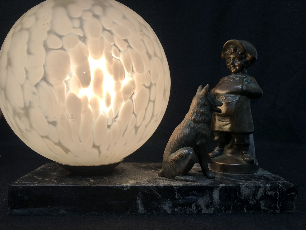 Lot 18 - An Art Deco style lamp on a black marble base with a brass dog and girl as decoration.